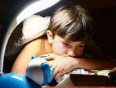 preteen handsome boy read book with lamp