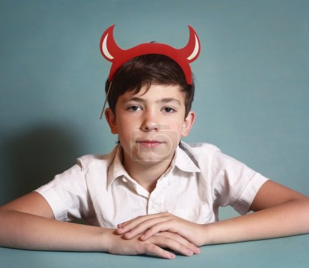 boy in white shirt and red horns