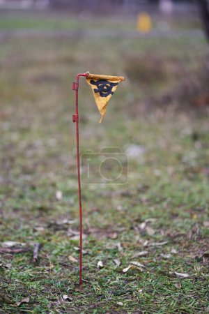 Photo for Close-up of a yellow sign with a skull warning of danger in a minefield - Royalty Free Image
