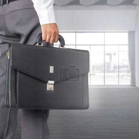 Photo pour Vue recadrée d'un homme d'affaires tenant une mallette dans son bureau - image libre de droit