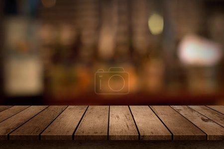 Foto de Mesa de madera con una vista de telón de fondo de bar bebidas borrosa - Imagen libre de derechos