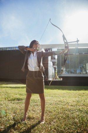 businesswoman practicing archery