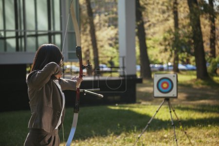 Photo for Businesswoman Pointing The Target With Bow And Arrow In Front Of Business Building - Royalty Free Image