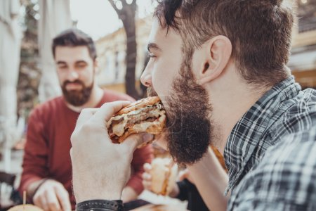Photo for Hipster Friends In Fast Food Rastaurant Eating Burgers - Royalty Free Image
