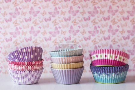 Colorful cupcake wrappers over a shelf with vintage background