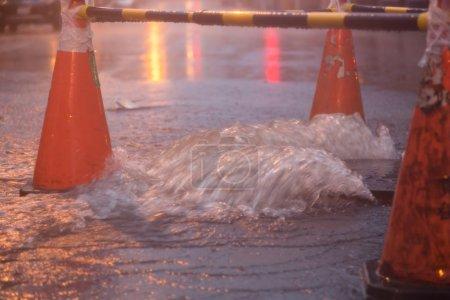 Photo pour Cônes orange autour de trou d'homme débordant pendant le typhon - image libre de droit