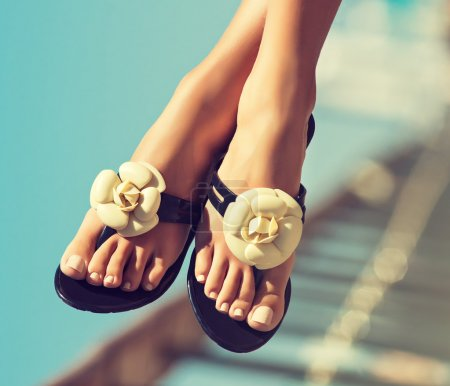 Photo pour Les filles élégantes jambes pédicure avec les ongles. Gracieux pieds femelles en beau flip flops sur la plage - image libre de droit