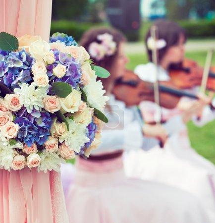 Photo pour Décoration de mariage fleurs arc. Violonistes de musiciens à la noce sur fond flou - image libre de droit