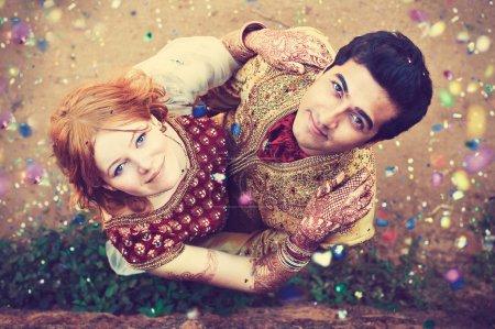 Photo pour Couple international embrassant, vue de dessus. Homme indien et fille européenne en robes de mariée indiennes. Mariage indien. Mariage interracial - image libre de droit