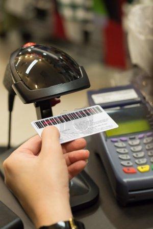 Photo pour Caissier à main barcode numérisation sur la carte de membre avec machine de carte de crédit sur le comptoir - image libre de droit