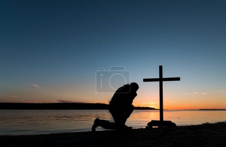 Photo for Beautiful clear sunset skies with a man kneels at a cross by a river shoreline. - Royalty Free Image