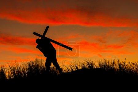 Photo pour Homme avec un portant une croix sur son dos au lever du soleil. - image libre de droit