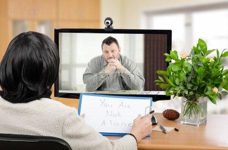 Photo pour Homme d'âge moyen assis dans le moniteur parle avec un psychothérapeute via le chat vidéo en ligne. Il avait l'air déprimé. psychiatre aux cheveux noirs détient un message écrit pour lui - Vous n'êtes pas seul. Plan horizontal à l'intérieur - image libre de droit