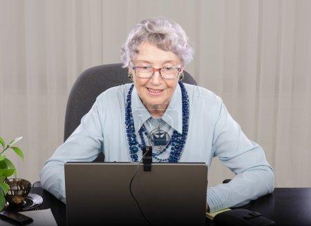 Photo pour Professeur de cheveux gris de glaces regardant l'écran d'ordinateur portatif. Elle enseigne l'anglais en ligne (ou toute autre) langue. L'enseignant porte le chemisier bleu et le collier bleu foncé de pierre avec le pendentif. - image libre de droit