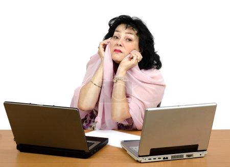Photo pour Mature femme aux cheveux noire assis en face de deux larmes d'ordinateurs portables et des hirondelles. La femme pleure parce que personne ne veut apprendre en ligne avec elle - image libre de droit