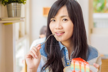 Photo for Beautiful smiling young asian woman eating cake in coffee shop - Royalty Free Image