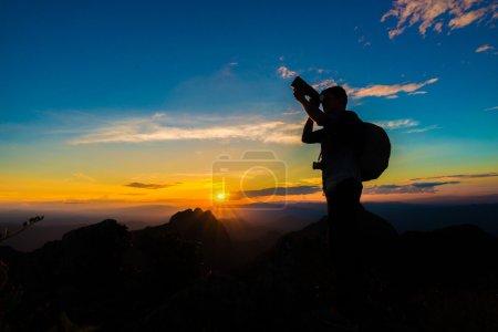 Photographer man on mountain reaches for the sun