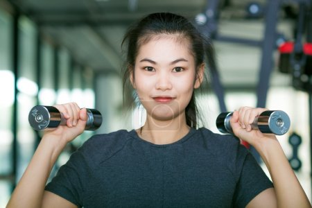 Body of young fit woman lifting dumbell.