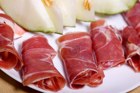 Closeup of rolled slices of cured pork ham jamon with melon