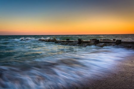 Waves and a jetty at sunset in the Atlantic Ocean at Edisto Beac