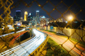 Chain link fence and view of I-35 and the skyline at night, seen