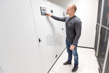 IT engineer adjusts air conditioner in datacenter