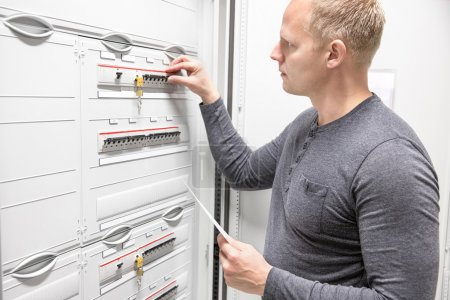 Technician works in large electric fuse cabinet