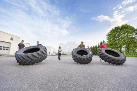 Workout team flipping heavy tires outdoor