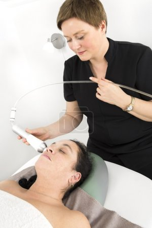 Woman client gets face slimming treatment at beauty clinic
