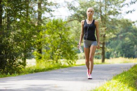 Photo pour Belle jeune femme blonde en forme marchant sur le sentier dans les bois. Entraînement extérieur . - image libre de droit