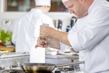Chef adding pepper on steak in the kitchen