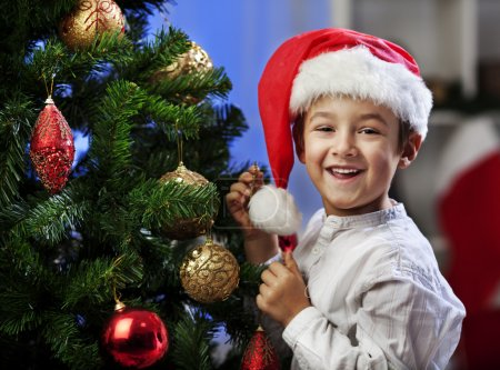 Young Boy Helping To Decorate The Christmas Tree