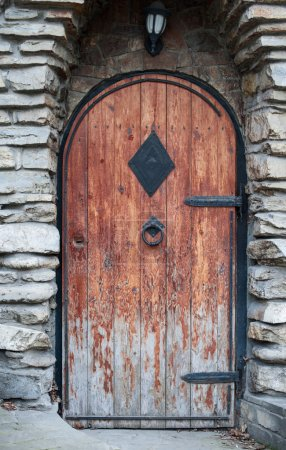 Old wooden door with wrought iron handle-beater