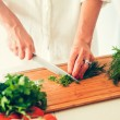 The woman is cooking at the kitchen ( slicing vege...