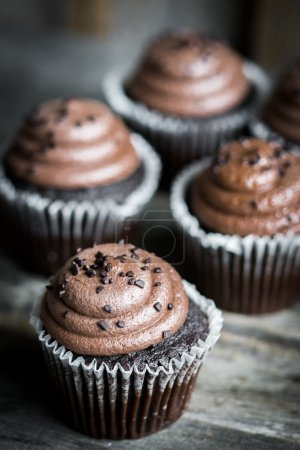 Chocolate cupcakes on rustic wooden background
