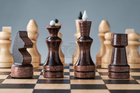 Photo for Wooden chess pieces on a chessboard, black pieces in a row, white pieces in the background, concept, strategy, planning and decision making. The concept of leadership and teamwork for success - Royalty Free Image