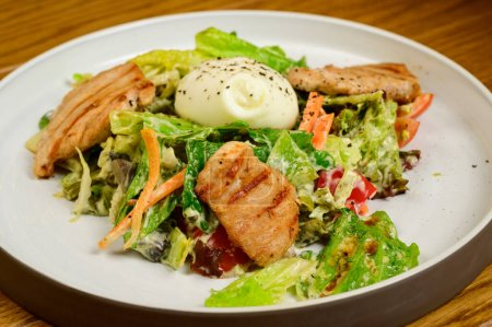 Photo for Caesar salad with croutons, quail eggs, cherry tomatoes and grilled chicken in wooden table.Delicious salad with chicken, nuts, egg and vegetables. - Royalty Free Image
