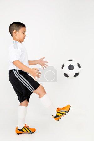 Portrait du petit garçon asiatique avec ballon cocker en uniforme de sport