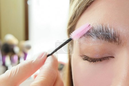 Beautiful young woman got correction of eyebrows in a beauty salon. eyebrow lamination