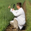 Agronomist in white coat looking through magnifier...