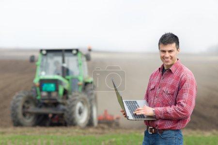 Farmer with laptop on field