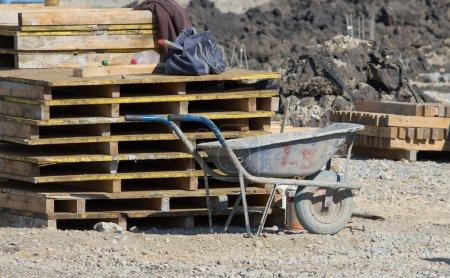 Photo pour Vieille brouette debout à côté de palettes en bois sur le chantier de construction - image libre de droit