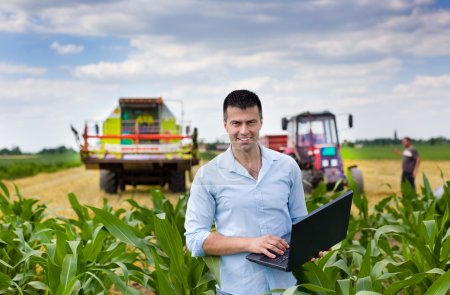 Young attractive farmer with laptop standing in co...