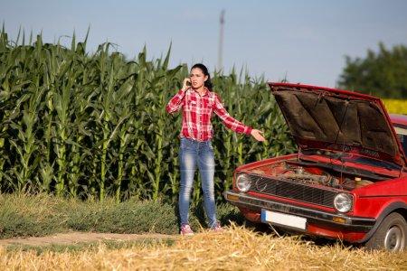 Girl on the phone beside broken car