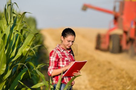 Beautiful girl agronomist with note book standing ...
