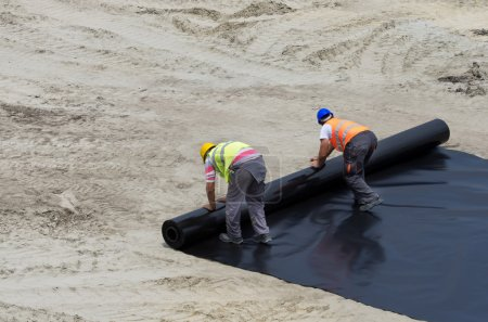 Workers unrolling foil