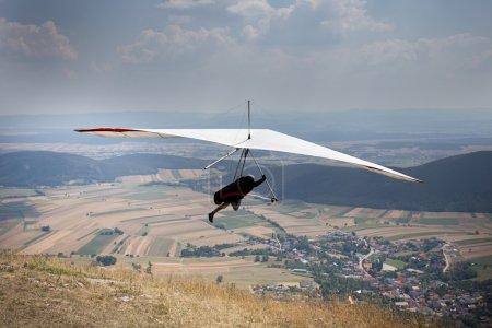Photo pour Deltaplane sauter du haut de la colline, village de champ vers le bas en arrière-plan - image libre de droit