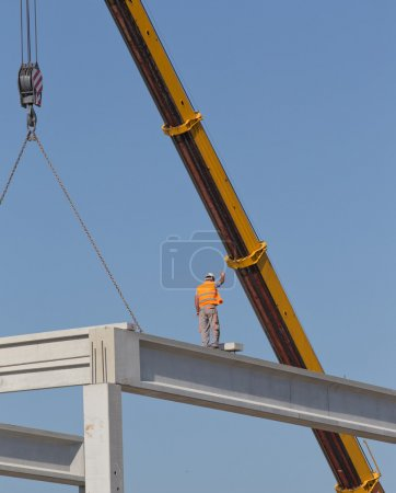 Height worker placing truss on building skeleton