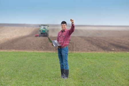Satisfied landowner with laptop  holding fist up i...