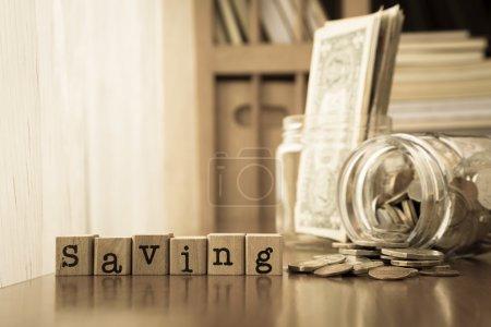 Foto de Guardar la palabra en lugar de sellos de goma en mesa con monedas y billetes de dinero tarros, sepia tonificación - Imagen libre de derechos